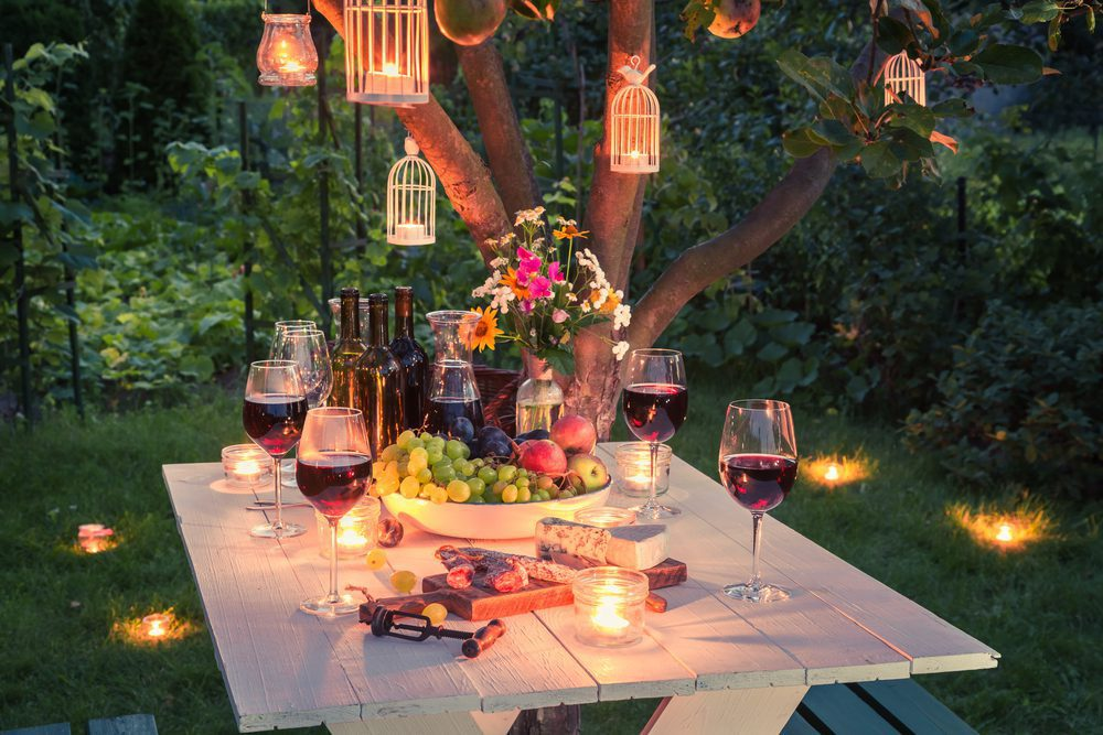 A table laid out with drinks & fairy lights for a garden party